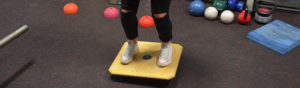 Physiotherapy patient balancing on exercise board