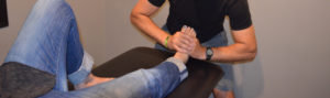 Physiotherapist massaging patient foot on treatment table