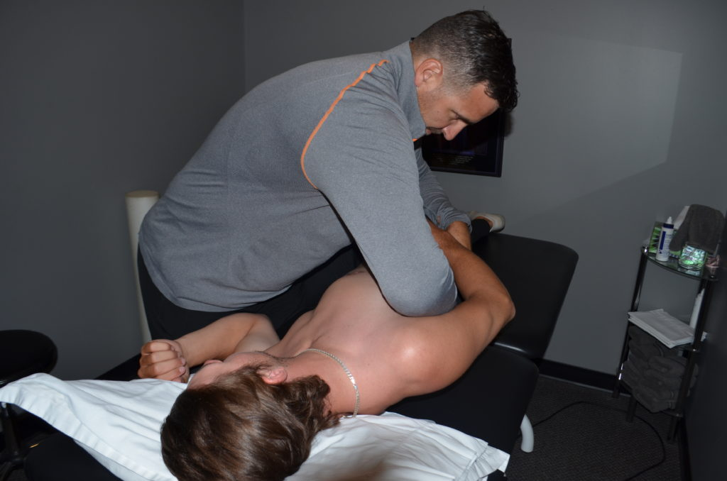 Physiotherapist treating patient on treatment table