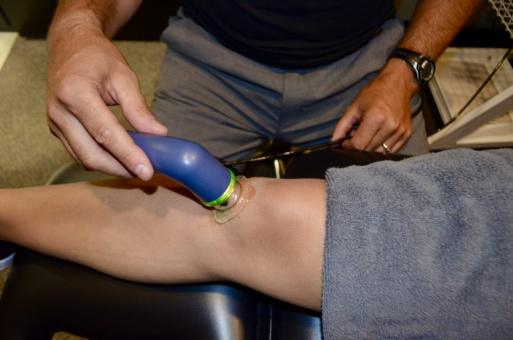 Physiotherapist providing ultrasound treatment to patient's knee