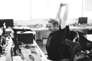 Person at desk stretching arms