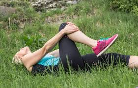 Woman in running attire stretching knee